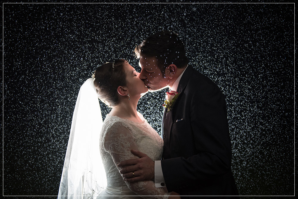 Rain shot with bride and groom illuminated